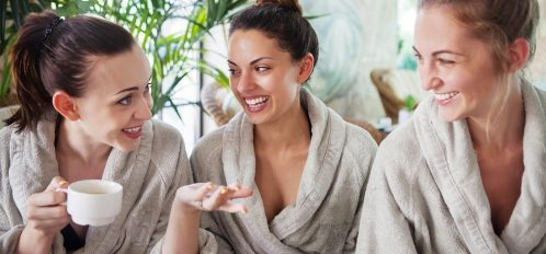 three girls wearing robes at a spa relaxing