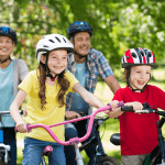 family of four wearing helmets and riding bikes