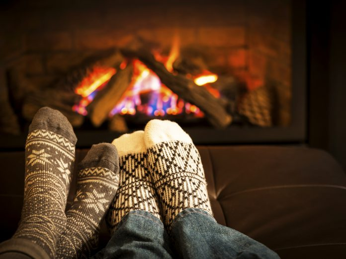 2 pair of feet in cozy socks warming up by a roaring fire